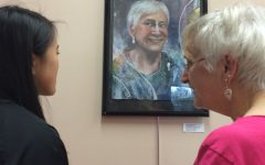 "Junior Cheryl Cai and senior citizen Millie Dusha converse over Cai's mixed media portrait, ""Millie"""
