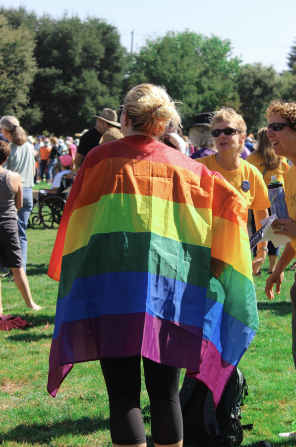 A woman runs across the field as her rainbow cape, fashioned from a Pride flag, flows behind her.