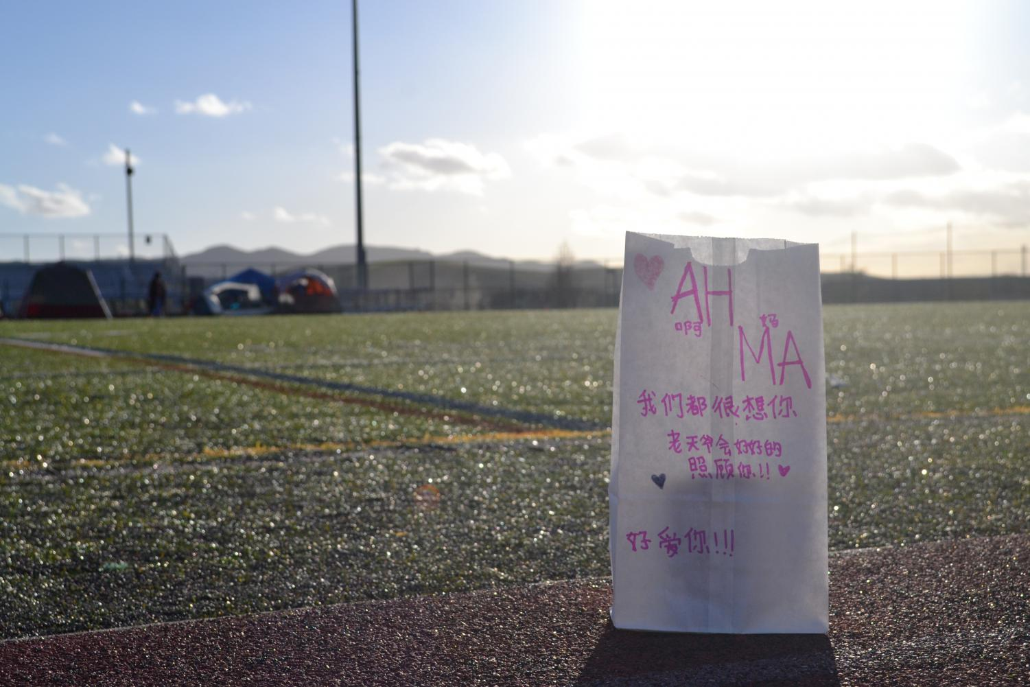 "Among the Luminarias lining the field, a particular one is written in the recipient's native language of Chinese. ""Mom / We miss you so much / God will take good care of you! / We love you!"" reads the pink text."