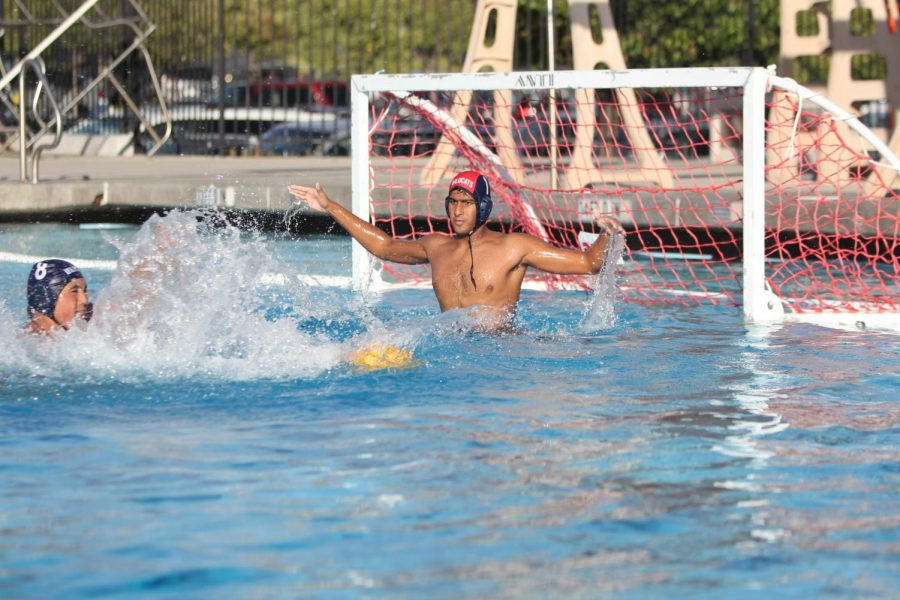 Senior Sharwin Patil jumps out of the water to block an incoming shot.