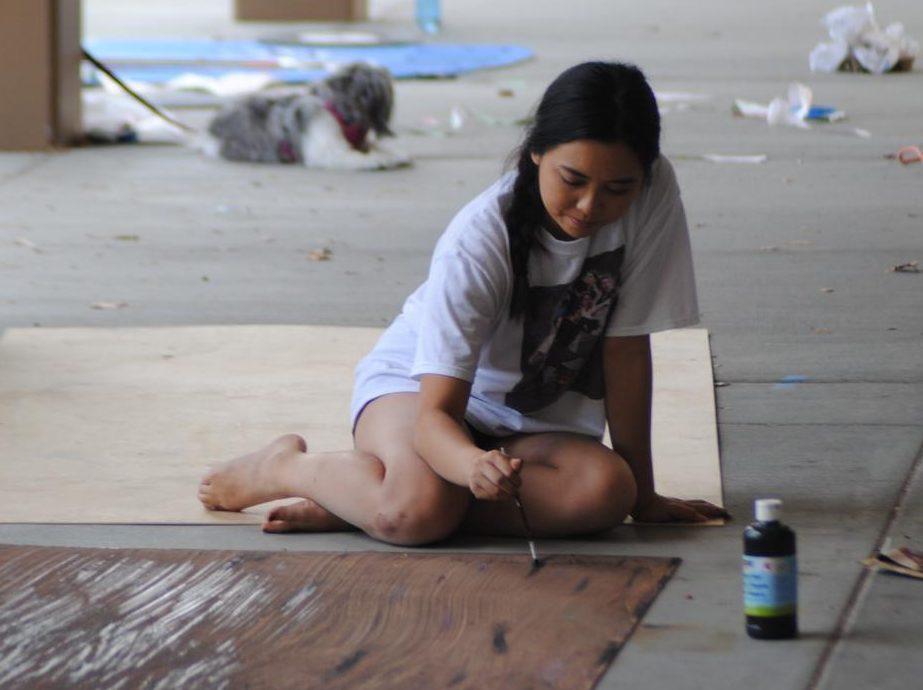 Francesca Apaya, senior, paints a decorative Homecoming banner.