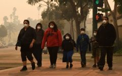 A family wearing N95 masks evacuates Paradise, which remains permeated with hazardous smoke from the Camp Fire.