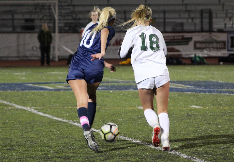 Junior winger Alyssa O'Brien dribbles past San Ramon Valley junior Hannah Sprinkle.