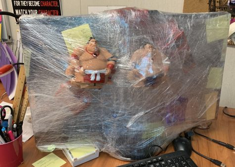 Mr. Clemente attaches robotic sumo wrestlers to Mrs. Oji-Marchese's desktop with several layers of saran wrap.