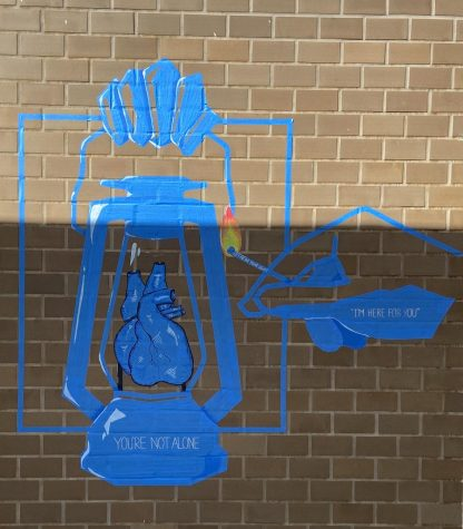 """Thanvi Anand, Rhea Park, Dorothy Yeung and Calista Koo created the stunning piece on a brick wall. A heart is formed, encased within a lantern. Inscribed in small letters on the lantern: """"You're not alone."""" On the reaching hand: """"I'm here for you."""""""