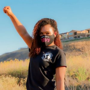 Tiana Day, wearing a mask and a shirt depicting nonprofit's logo, raises her fist in a sign of power.