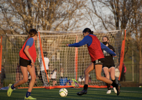 Two San Ramon FC players attempt to score a goal during a team shooting drill.