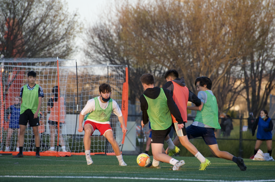 In a competitive scrimmage within a San Ramon FC team, players fight their way to either score or defend the goal, leading to momentary contact.