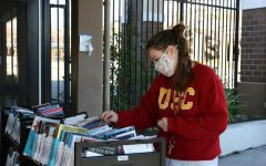 School librarian, Allison Hussenet, looks through books ready for curbside pickup as part of the library's ongoing efforts to keep remote learners reading.
