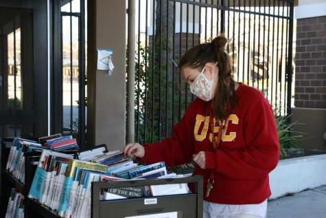 School librarian, Allison Hussenet, looks through books ready for curbside pickup as part of the library