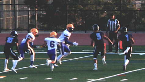 Wildcat running back Matthew Gonsalves (5) rushes forward with quarterback Aditya Ved (1), meeting Cougar linebacker Joshua Limtiaco (6) and others at the goal line.
