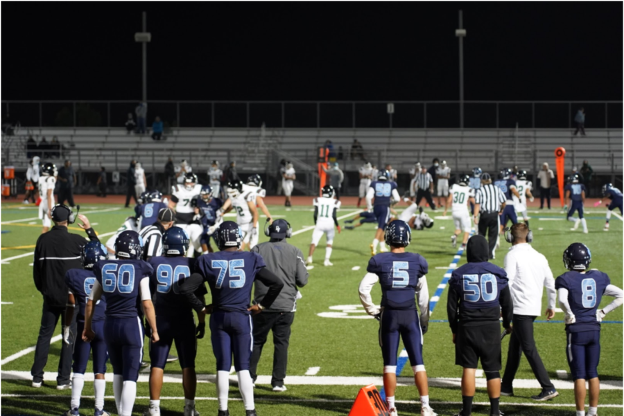 Wildcat Varsity coaches and players Devin Garica (9), Jake Masse (60), Theodore Leong (90), Erimi Oshewa (75), Matthew Gonsalves (5), Angel Brito (50) and RJ Pallen (8), watch the Red Devil carry the football against the Wildcats defending on the field.