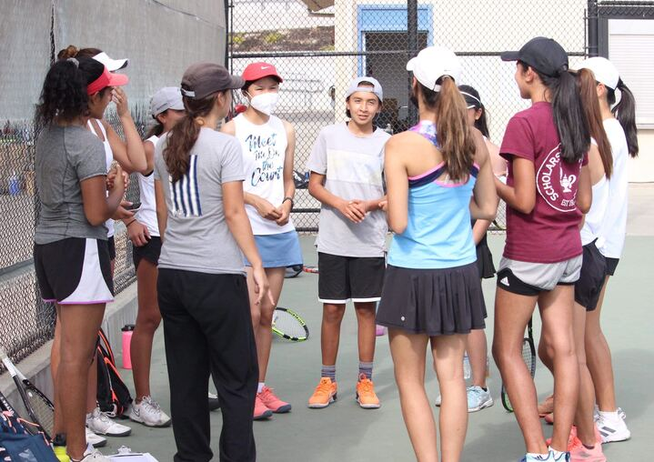 Varsity+women%E2%80%99s+tennis+huddles+in+a+circle%2C+performing+their+team+chant+before+the+match.